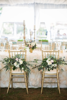chiavari chairs with flowers and baby blue eucalyptus marking bride and groom chairs
