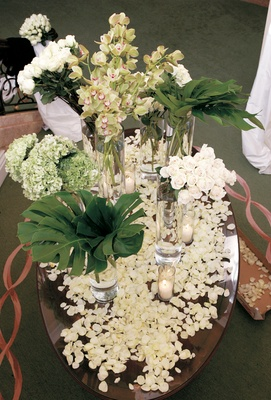 Table covered with white rose petals and decorated with roses, hydrangeas, orchids, and fronds