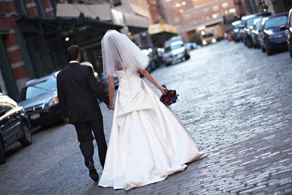 bride and groom walk down city street