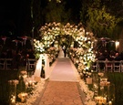 Outdoor winter wedding at The Beverly Hills Hotel with candles, flower petals, white aisle runner