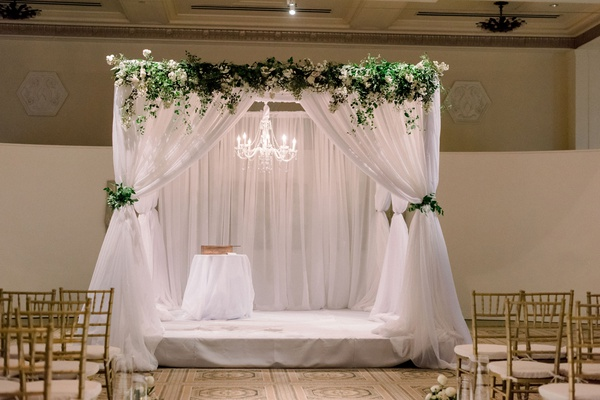 interfaith ceremony structure with white drapery, greenery, and chandelier