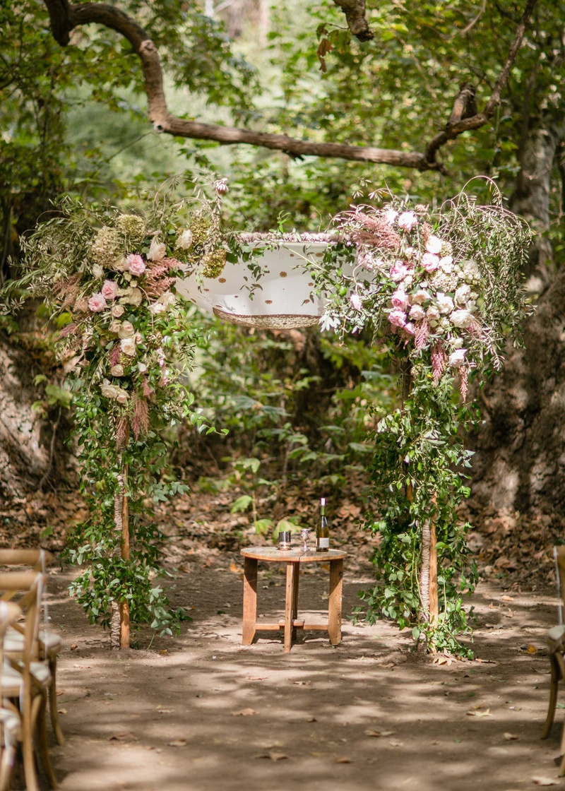 Outdoor Jewish wedding ceremony chuppah made of tree branches pink flowers greenery wood table under