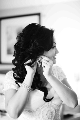 Black and white photo of bride putting on earrings
