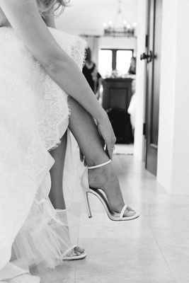 Black and white photo of bride fastening Stuart Weitzman heel