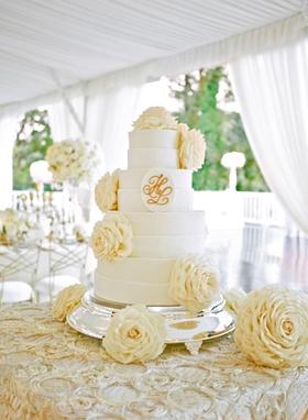 White cake with monogram and glamelia rose decorations