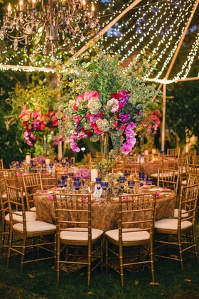 Tent wedding reception with gold rosette table linens, tall green flower arrangements, string lights