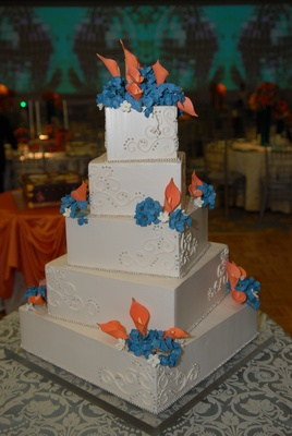 White wedding cake with orange and blue sugar flowers