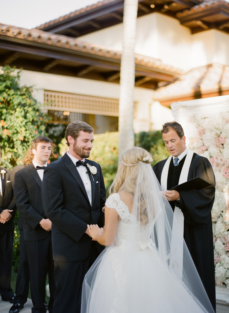 Bride in a Monique Lhuillier gown and groom in a black tuxedo at a garden ceremony