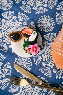wedding reception styled shoot tropical theme blue linen gold flatware orange sunglass and toucan