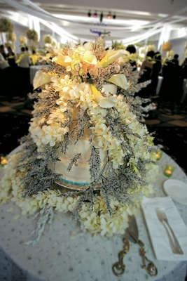 Wedding cake covered in flowers and frosted twigs
