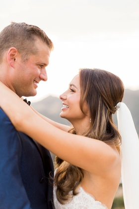 Bride with veil hair down curls smiling at groom in navy suit looking into eyes at outdoor venue
