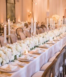 long wedding reception head table lined with lush white flowers interspersed with tapered candles