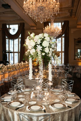 silver linens, centerpiece with large white flowers and cascading garland of orchids