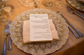 silver-and-gold charger with blush napkin and menu