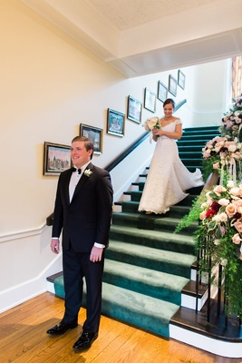 Bride in Legends Romona Keveza lace off shoulder wedding dress on staircase first look photo