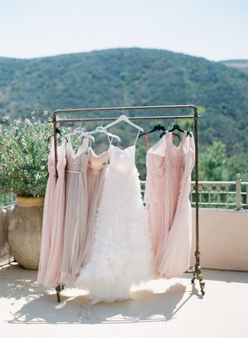 Monique Lhuillier wedding dress and pink and taupe bridesmaid dresses BHLDN on clothes rack view