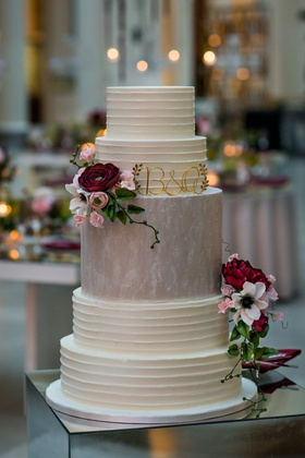 Tall white wedding cake with middle tier in grey and dark flowers gold monogram