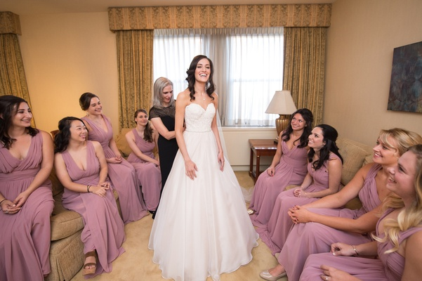 bride in essence of australia wedding dress, mother of the bride helps with dress, bridesmaids watch