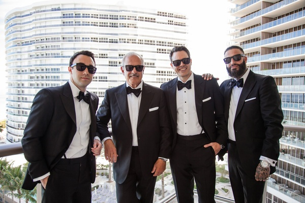 groom and groomsmen in tom james tuxedos in sunglasses on balcony