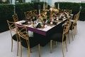 Black velvet and gold back chairs around white marble table with fall hued centerpiece candlesticks