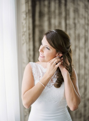 Bride in bridal suite hair pulled back soft curls The White Dress bridal gown ring bracelet headband