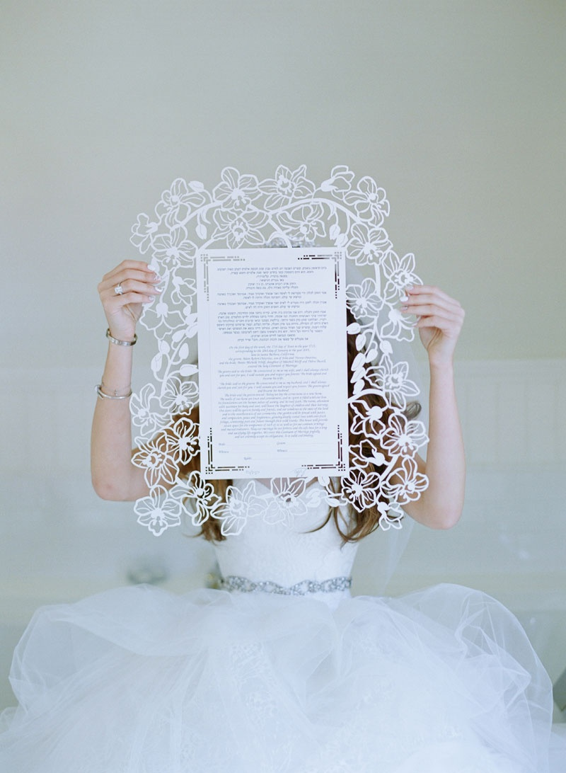 Bride in voluminous white Vera Wang ball gown holding lasercut chuppah with flower motif