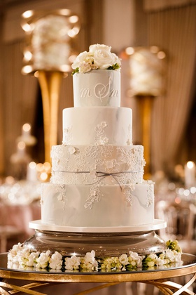 wedding cake with floral motif bow ribbon and fresh flower cake topper monogram icing frosting