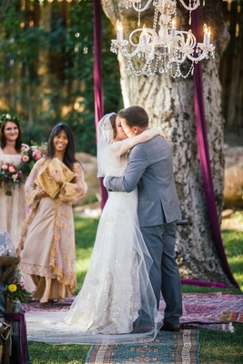 Bride in a Claire Pettibone dress with gold and silver embroidery, veil kisses groom in grey suit