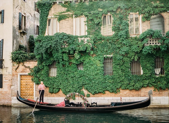 Venice Italy wedding gondola decorated with greenery and flowers man in red and white stripe shirt