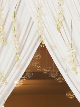 clear geometric shaped escort cards suspended from hanging fabric and long stems with white blooms