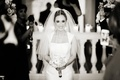 Black and white photo of bride walking down aisle with veil