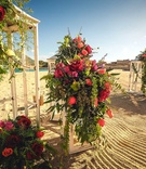 white lanterns with cascading floral arrangements of red and orange flowers including roses on beach