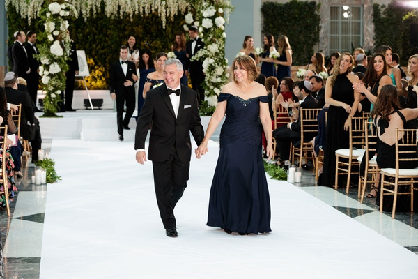 father of groom in tuxedo mother of groom in off shoulder navy evening gown aisle recessional