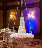 Light blue and gold wedding cake on top of chandelier display pink peony flowers and crystals