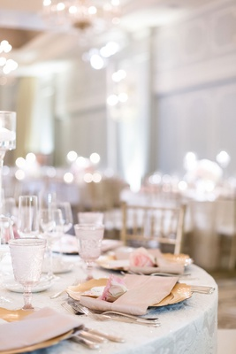 wedding reception ballroom round table texture linen gold charger pink rose and napkin glassware