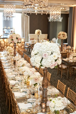 gold chiavari chairs, rose centerpieces on long family tables with mirror tops under chandelier