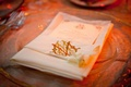 Wedding reception place setting with white napkin decorated with the couple's gold monogram