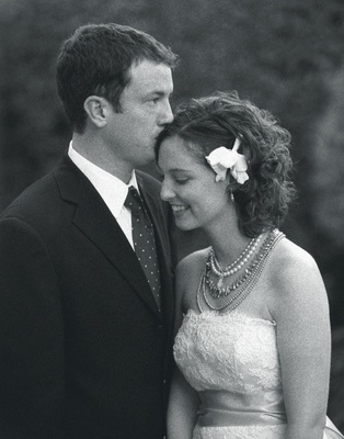 Black and white photo of groom kissing bride's forehead