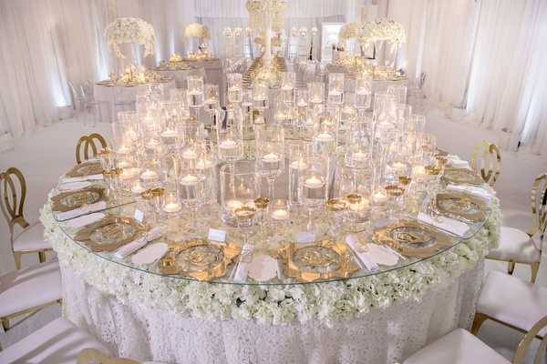 Round table with textured linens, white flowers and glass tabletop floating candles gold chargers