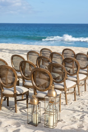 beach wedding ceremony decor round back wood cane chairs white cushions gold lantern white sand