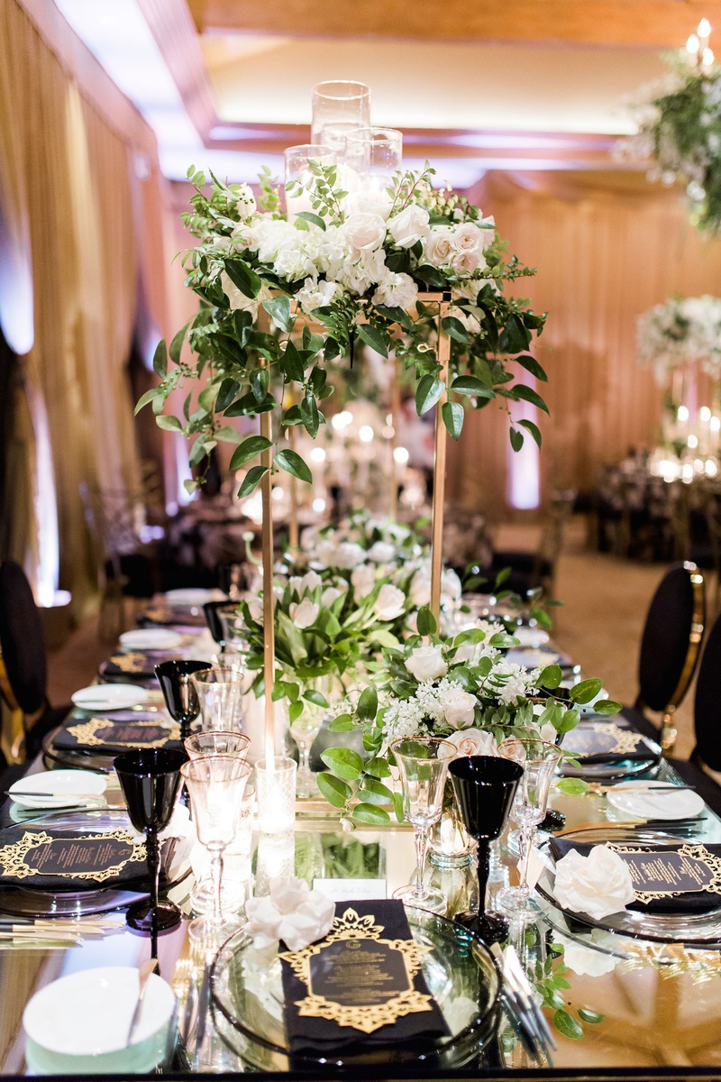 Gold stand on wedding table white rose hydrangea greenery candles tulip black goblet chairs menus