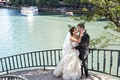 a bride and groom in full wedding dress tux hugging one another on steps to lake in Chicago