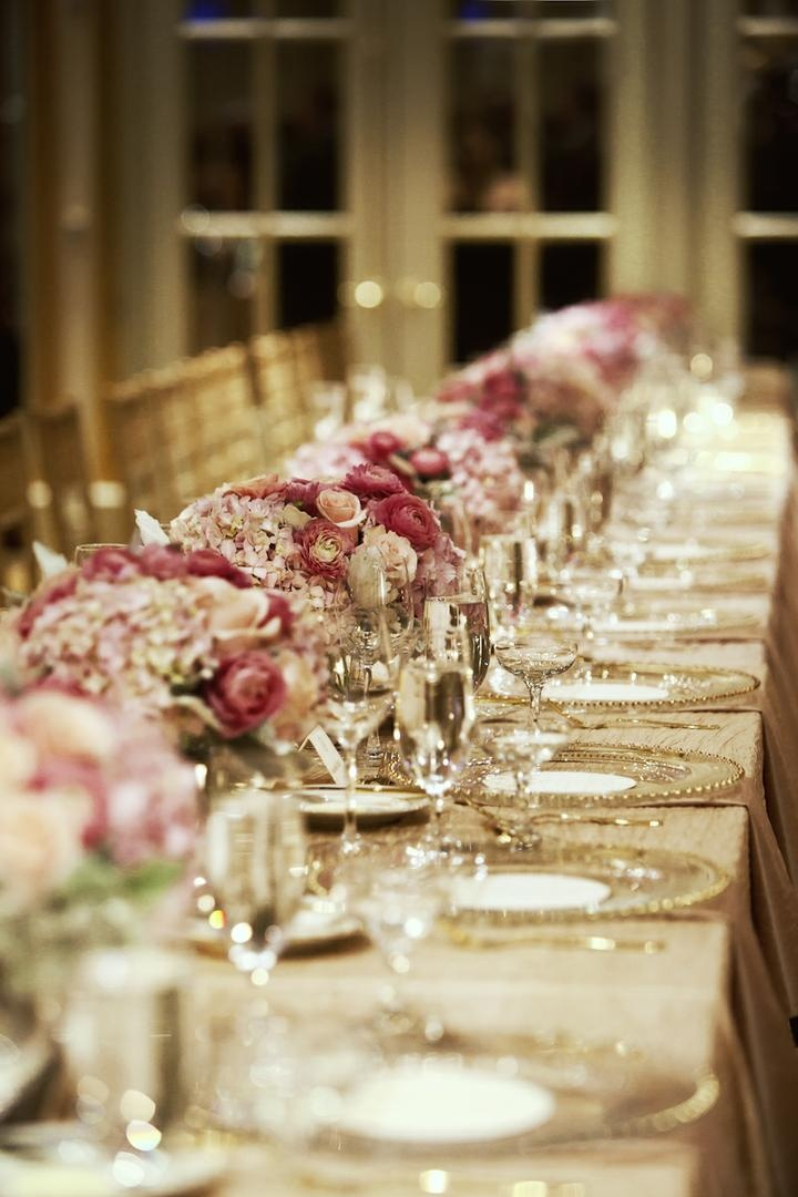 Gold-rimmed charger plates and pink floral arrangements