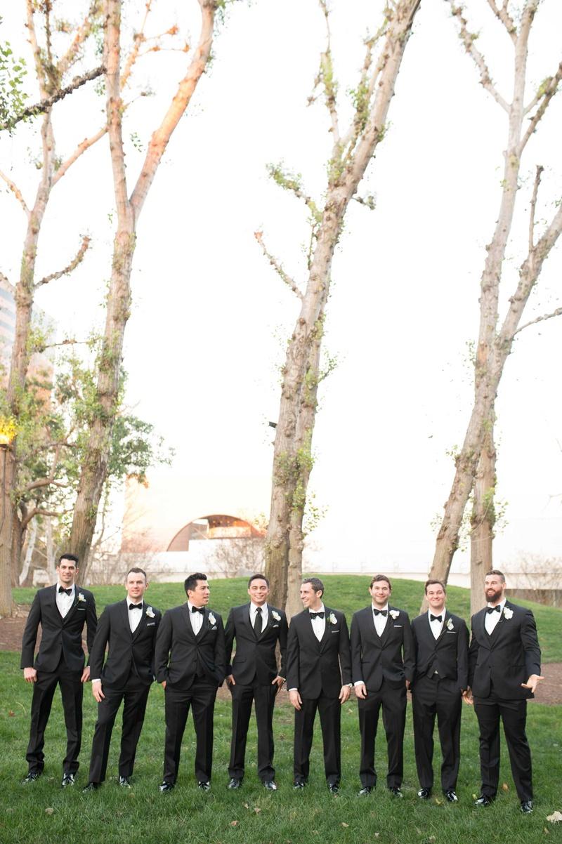 Cute men in tuxes standing in green grass