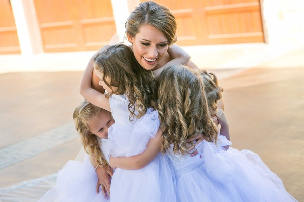 Bride smiles while holding three flower girls with lavender dresses and ringlets