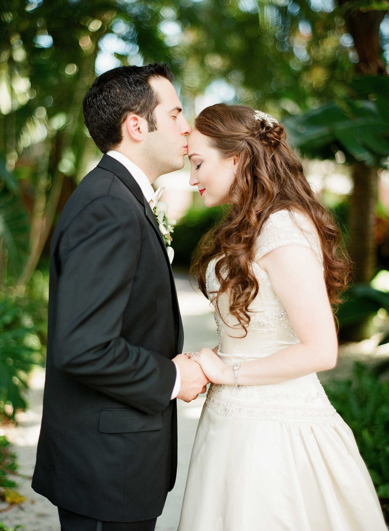 Couples photos groom holds brides hand kisses on forehead groom holding brides hand kiss on forehead florida wedding beaded bridal gown black suit half up junglespirit Image collections
