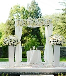 All-white wedding ceremony arch and flowers