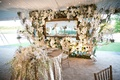 Large floral wall with grapewood, white orchids and hydrangeas, mirror behind sweetheart table