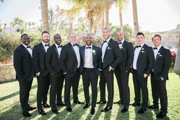 a groom in a blue and black tuxedo stands groomsmen classic black tuxedos outdoor near palm trees