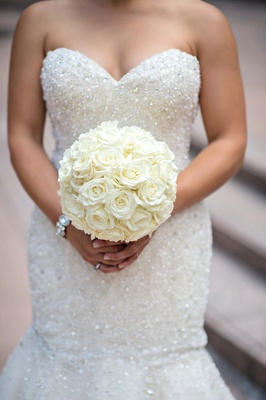 Bride in beaded wedding dress holding roses
